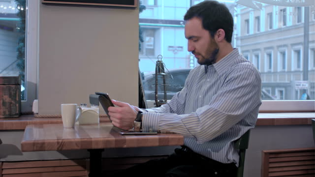 yawns young man using tablet computer in cafe video