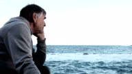 50 year old man contemplating the sea video