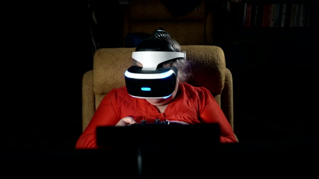70 year old woman playing video game uses VR headset and gaming controller video