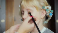 5 years old girl doing makeup. curlers on her head video
