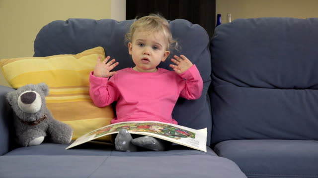 2 years old lovely baby girl sit on sofa read story book and show emotions. video