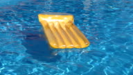 Yellow air bed raft floating on a swimming pool video