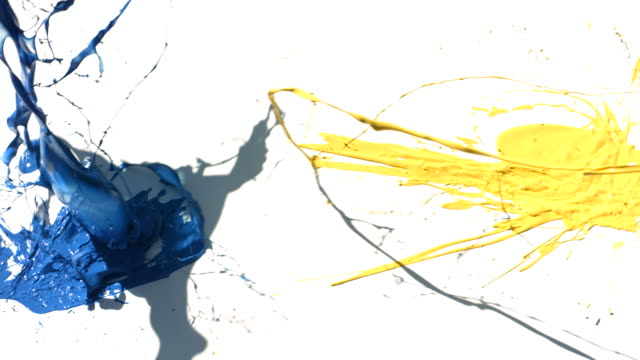 Yellow and blue paint splattering on white background video
