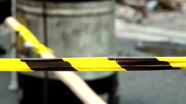 Yellow black striped tape outdoors, police investigation line video