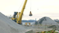 Yellow excavator pours a pile of rubble in front of a river. Its bucket suspended on cables. video