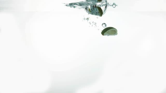 Yellow Lemons, citrus limonum, and Green Lemons, citrus aurantifolia, Fruits falling into Water against White Background, Slow Motion 4K video