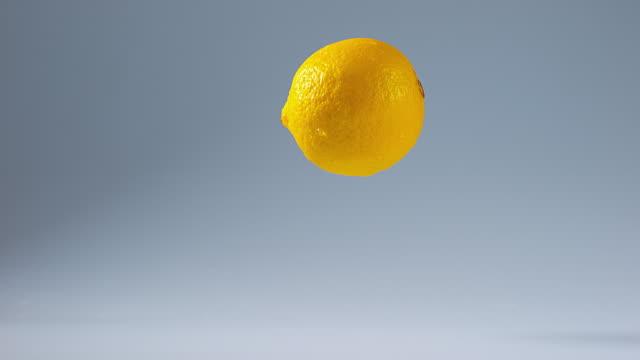 Yellow Lemons, citrus limonum, Fruits falling on Water, Slow Motion 4K video
