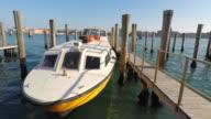 Yellow motor boat moored at boats wharf, Venice, Italy video