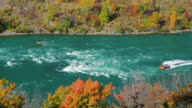 Yellow pleasure boat sails along the Niagara River downstream of Niagara Falls. The river divides the USA and Canadacan. Be seen autumn forest. ProRes 422 HQ 10 bit video video