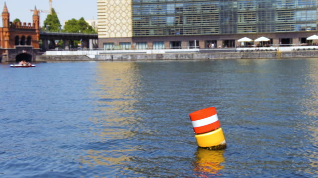 Yellow red and white steel navigational floating buoy in the blue Spree river water video