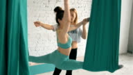 Yoga Choach Helps Female Student To Stretch Legs And Do Splits On Aerial Silks video