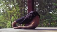 Yogi man at the park takes Halasana exercise video