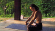 Yogi sitting on a mat in the park and an exercise video