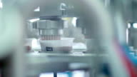 Yogurt is poured into package. Dairy product at production line. Packaging process of yogurt in the plastic container. Food packaging line at dairy factory. Production line at food processing plant. Industrial equipment at food factory. Packing machine video