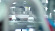 Yogurt is poured into the package. Food packaging line at dairy factory. Dairy product at production line. Packaging process of yogurt in the plastic container. Production line at food processing plant. Industrial equipment at food factory. Packing machin video