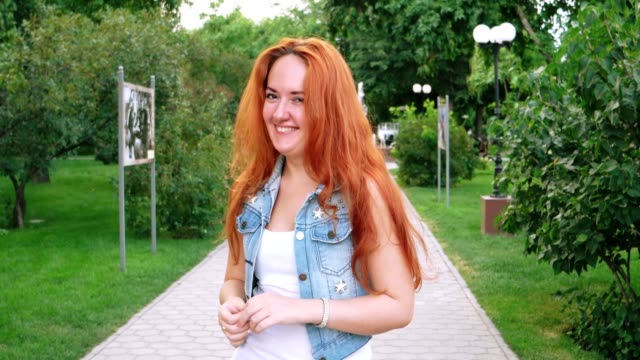 Yoiung beautiful redhead girl in the spring garden happy video
