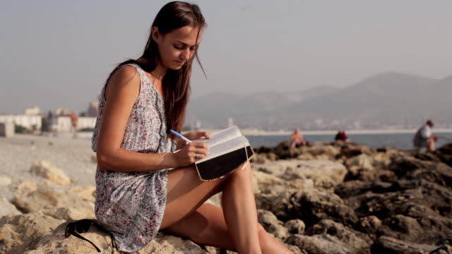 Yong woman making notes in diary on the beach video