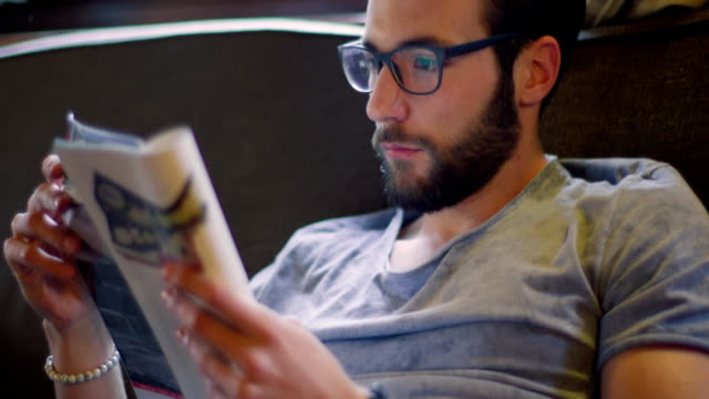Youg millennial man relaxing reading magazine newspaper at home in casual dressing. 4k video video