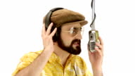 Young 70s bearded speaker man dressing hat and yellow floral orange vintage shirt talks to microphone with headphones - isolated-on-white HD video footage video