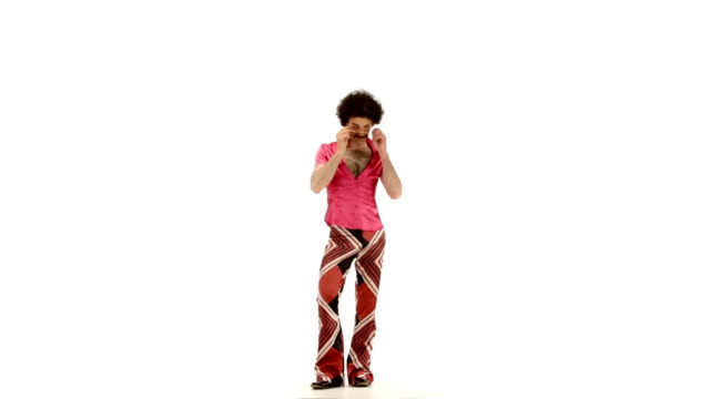 Young 70s curly hair man dressing fuchsia vintage shirt and bell bottoms portrait - isolated-on-white HD video footage video