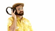 Young 70s seductive bearded man close-up dressing dressing hat and yellow floral orange vintage shirt listen music - isolated-on-white HD video footage video