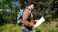 Young active man walking through highland forest and checking his way with paper terrain map video