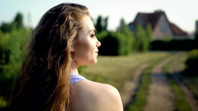 Young, adorable woman slowly walks down the countryside road and gives a cunning look back video