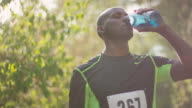 Young adult african american runner drinking water after race video