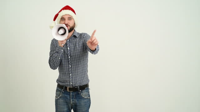young adult beard man showing an copy space with megaphone in a hat santa claus on a grey background video