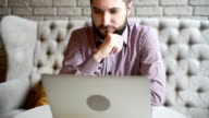young adult bearded man with a laptop video