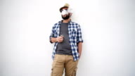 young adult bearded man with an electronic cigarette standing near the wall video