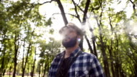 young adult bearded man with the e-cigarette is in the park and enjoy video