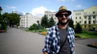 young adult bearded man with the e-cigarette is the city and smiles video