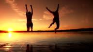 Jeune adulte couple de sauter dans le lac. - Vidéo