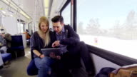 Young adult couple ride a train and play on tablet video