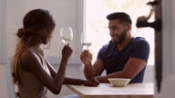 Young adult couple sit drinking wine and talking in kitchen, shot on R3D video