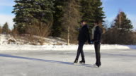 Young adult couple skating together in winter on ice.. video