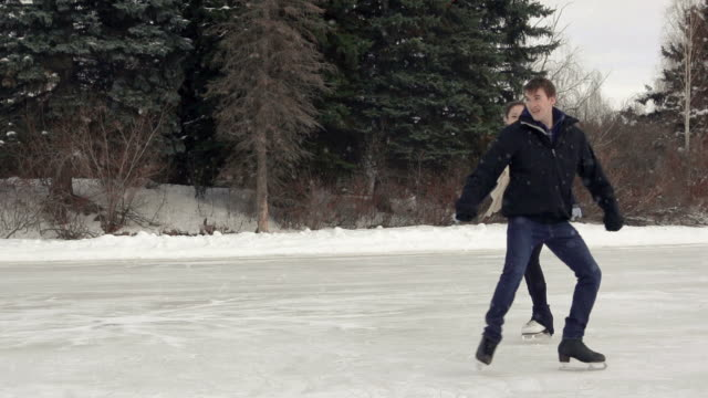 Young adult couple skating together on the ice. video