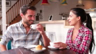 Young adult couple talking at a table in a cafe video