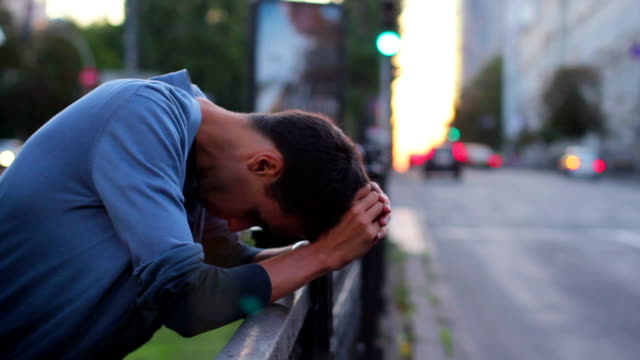 Young adult depression, heart break standing fence traffic cars video