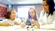Young adult female Asian teacher teaches elementary and junior high student about a molecular structure in science class video