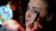 Young adult female doing her make up applying eyeshadow to eyelids video
