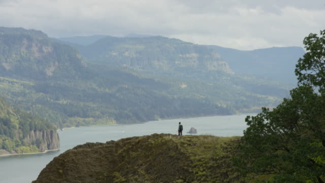 Young adult female hiker hiking along ridge with scenic background video