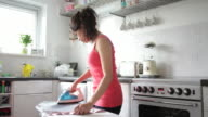 young adult female ironing clothes in Kitchen video