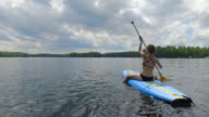 Young adult female paddle boarding outdoors during summer video