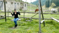 Young adult female swinging on a swing in the countryside with horses in the background video
