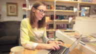 Young adult female using laptop in a bookshop. video
