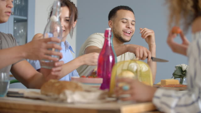Young adult friends drinking and eating at a friends dining table video
