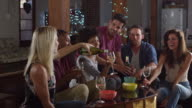 Young adult friends drinking and eating snacks at home, shot on R3D video
