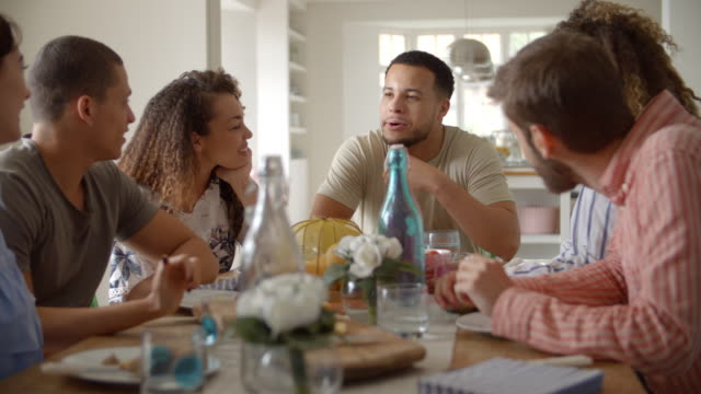 Young adult friends talking at a table over lunch, close up video